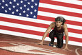 Runner on a track in starting block in front of us flag Royalty Free Stock Images