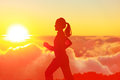 Runner woman running in sunshine sunset fitness athlete training trail running marathon in mountains above the clouds in beautiful Royalty Free Stock Image