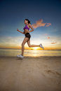 Runner woman on the sea beach at sunset Royalty Free Stock Photo