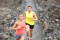 Runners couple running on trail in cross country run outdoors training hawaii big island for marathon or triathlon fit young Stock Images