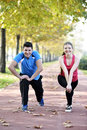 Runners couple sport running on trail in cross country run outdoors training on jogging track fit young fitness model men and Stock Image