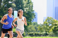 Runners jogging in new york city central park usa healthy couple of yorkers athletes running summer sun working out a Royalty Free Stock Image