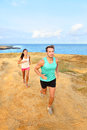 Runners running outside by ocean runner couple athletes men and women jogging outdoors in beautiful landscape on green sand beach Stock Image