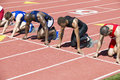 Runners waiting at starting blocks group of multiethnic male athletics Royalty Free Stock Image