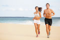 Runners young couple running on beach athletic attractive people jogging in summer sport shorts enjoying the sun exercising their Stock Photo