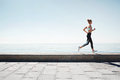 Running asian woman. Female runner training outdoors seaside Royalty Free Stock Photo