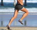 Running on the beach young athletic woman on the beach Stock Photos