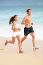 Running couple jogging on beach runners sport training together outside on beautiful beach fit athlete fitness model men and Stock Photo