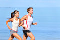 Running couple jogging on beach runners training together man and women joggers exercising outdoors Royalty Free Stock Images