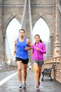 Running couple jogging in new york city training for marathon runners rain outside asian women and caucasian men runner and Stock Photo