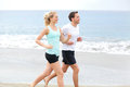 Running couple runners jogging on beach training together man and women joggers exercising outdoors Royalty Free Stock Photo
