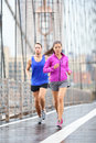 Running couple runners jogging outside in rain woman and men runner athletes training outdoor for marathon on brooklyn bridge new Royalty Free Stock Photo