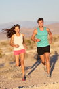 Running couple runners jogging on trail run path outside in beautiful nature asian women runner and caucasian male fitness sport Stock Photography