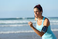 Running with earphones and sport band fitness woman on beach while listening music sporty girl wearing arm for smartphone Royalty Free Stock Photo