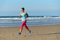 Running for fitness on beach woman while listening music through earphones sporty girl wearing arm sport band smartphone Stock Photo