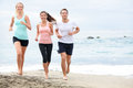 Running friends on beach jogging group training exercising runners training outdoors living healthy active lifestyle multiracial Royalty Free Stock Photos