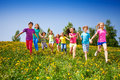 Running happy kids holding hands in green field Royalty Free Stock Photo