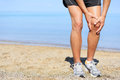 Running injury man jogging with knee pain close up view of runner injured on the beach clutching his in male Royalty Free Stock Image