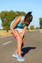 Running knee injury and pain sport woman runner in while training for marathon in country road caucasian female athlete Royalty Free Stock Photo