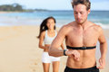 Running man jogging using heart rate monitor young men on beach handsome shirtless male runner working out outside by the ocean Royalty Free Stock Image
