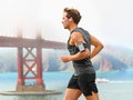 Running man male runner in san francisco listening to music on smart phone sporty fit young jogging by bay and Stock Photography