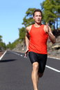 Running man sprinting fast at speed male athlete runner sprinter training on road outdoors during workout strong male fitness Royalty Free Stock Images