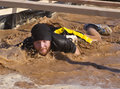 Running and obstacle course runners are challenged to run jump climb crawl through a long Royalty Free Stock Images