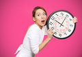 Running out of time closeup portrait woman worker holding clock looking anxiously pressured by lack isolated pink background human Royalty Free Stock Images