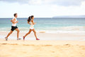 Running people woman and man athlete runners women men jogging in sand on beach fit young fitness couple exercising healthy Stock Photo