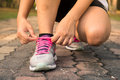 Running shoes - woman tying shoe laces. Closeup of female sport fitness runner getting ready for jogging outdoors on forest. Royalty Free Stock Photo