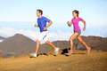Running sport runners couple in trail run outside amazing nature fit young sports multiracial fitness training cross Royalty Free Stock Image