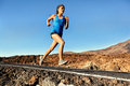 Running sprinting woman female runner training outdoors jogging on mountain road in amazing landscape nature fit beautiful fitness Stock Photos