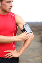 Running training music runner man listening to adjusting settings on armband for smartphone fit male fitness model working Royalty Free Stock Images