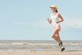 Running woman beautiful sports girl runs along the beach Royalty Free Stock Photo