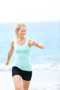 Running woman jogger with heart rate monitor watch looking at outside jogging on beach female fitness runner girl training Royalty Free Stock Photo