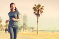 Running woman jogging on beach boardwalk healthy lifestyle girl runner training outside working out mixed race asian caucasian Royalty Free Stock Photo