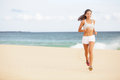 Running woman jogging on beach female runner training outside in summer fit young female sport fitness model exercising in full Royalty Free Stock Photos