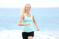 Running woman jogging outside on beach female fitness runner girl jogger training outdoors listening to music in earphones Stock Images