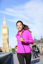 Running woman in london near big ben living healthy lifestyle female runner jogging jacket urban fitness girl smiling happy Stock Photography