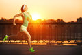 Running woman runner is jogging in sunny bright light on sunris sunrise female fitness model training outside the city a quay Royalty Free Stock Photos