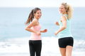 Running women jogging training on beach girlfriends runners exercising together smiling happy looking at camera two beautiful Royalty Free Stock Image