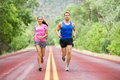 Running young couple outside jogging happy smiling multicultural exercising fitness on road in pretty nature asian female model Royalty Free Stock Image