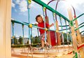 Runny on playground constraction happy running over the suspension bridge little three years old child sunny day Stock Image