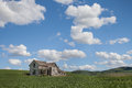 Rural abandoned farmhouse old dilapidated wood frame house in middle of green field of summer in the country with blue sky with Stock Photos