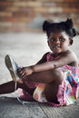 Rural african child young girl tying shoelace and putting shoot on foot in setting Stock Photo