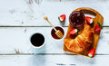 Rural breakfast with croissant top view of cup of coffee jam honey and strawberries on rustic white wooden table background layout Stock Photo