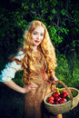 Rural girl beautiful young woman with magnificent blonde hair standing outdoor with a basket with apples countryside Royalty Free Stock Images