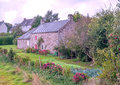 Rural house in the french brittany stone houses with gardens and flowers on a cloudy day Stock Images