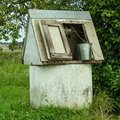 Rural landscape. Old-fashioned well with a metal bucket in the g Royalty Free Stock Photo