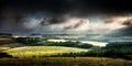 Rural landscape stormy daybreak lit up with morning sunshine and clouds Stock Photo